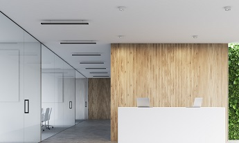 Front view of a white reception desk with two laptops standing on it in front of a wooden office wall. There are glass wall offices to the left. 3d rendering, mock up